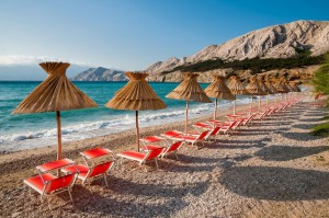sunshades-and-orange-deck-chairs-on-beach-at-baska-krk-croat-pablo-debat-fotolia.com